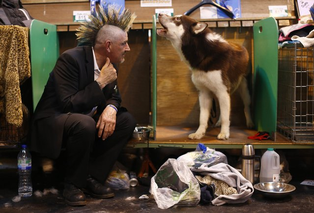 Pete Dowling sits with Zoran a Canadian Eskimo dog during the first day of the Crufts dog show in Birmingham, central England March 6, 2014. (Photo by Darren Staples/Reuters)
