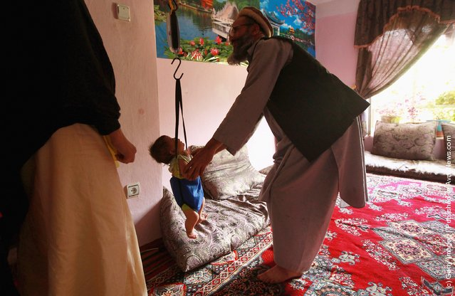 An Afghan vollunteer weighs a child at a USAID-funded health help center