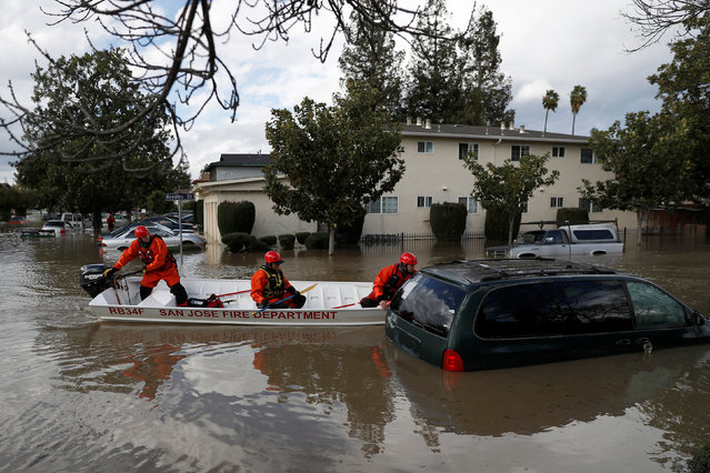 Firefighters with the San Jose Fire Department inspect a vehicle partially submerged in flood water after heavy rains overflowed nearby Coyote Creek in San Jose, California, U.S., February 21, 2017. (Photo by Stephen Lam/Reuters)
