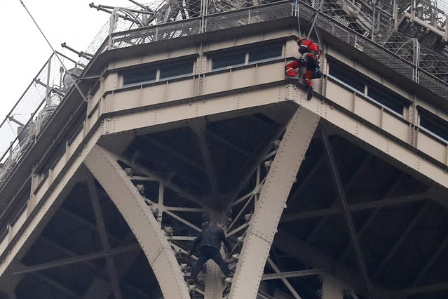 A rescue worker, top in red, hangs from the Eiffel Tower while a climber is seen below him between two iron columns Monday, May 20, 2019 in Paris. The Eiffel Tower has been closed to visitors after a person has tried to scale it. (Photo by Michel Euler/AP Photo)