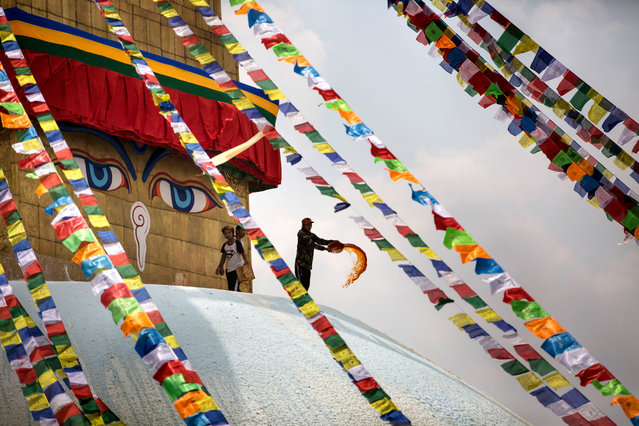 A pilgrim spreads color at the Bauddhanath stupa in Kathmandu, Nepal, 10 April 2019. Bauddhanath is one of the largest spherical stupas in Nepal and a United Nations Educational, Scientific and Cultural Organization (UNESCO) world heritage site. Buddhist pilgrims perform worship by offering Syampur, cloth for the stupa, and Lungtar, prayer flags, with a belief that doing so, bad luck will be negated from their life. (Photo by Narendra Shrestha/EPA/EFE)