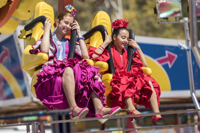 Young girls in traditional costumes enjoy fairground rides at the Feria de Abril, Andalucía's April celebration in Seville, Spain on April 14, 2016. (Photo by Zuma/Rex Features/Shutterstock)