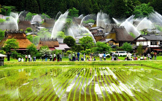 Water are discharged during a biannual fire exercise at Kayabuki no Sato, thatched roof farmhouses on May 20, 2019 in Nantan, Kyoto, Japan. (Photo by The Asahi Shimbun via Getty Images)