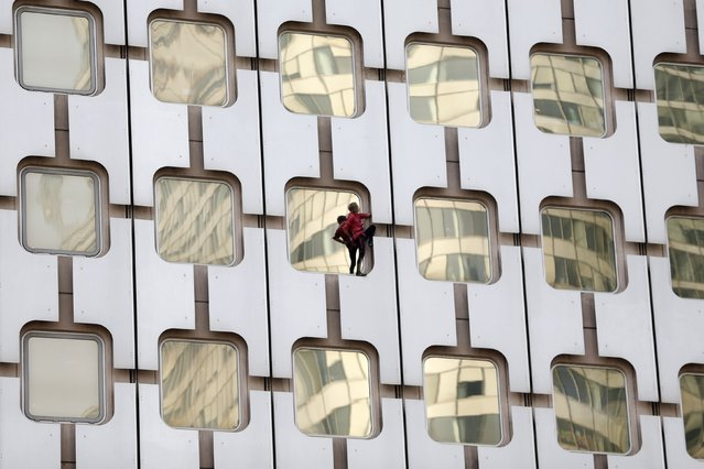 """French climber Alain Robert, also known as """"Spiderman"""", scales the 152 metre Ariane Tower at La Defense financial and business district outside Paris March 27, 2014. (Photo by Charles Platiau/Reuters)"""