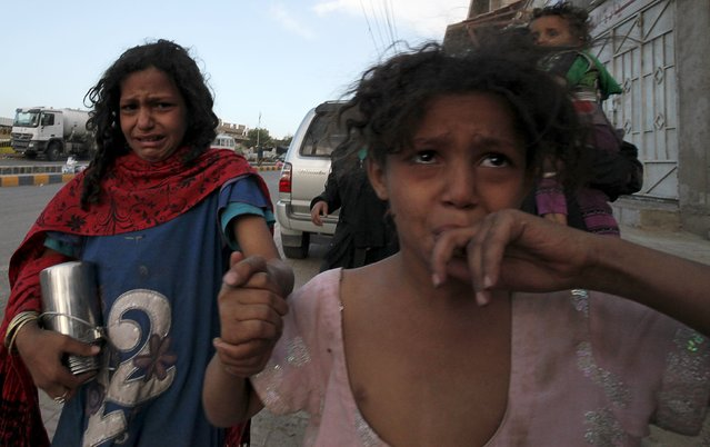 A girl cries next to her mother after fleeing from an air strike on an army weapons depot in Yemen's capital Sanaa May 11, 2015. (Photo by Mohamed al-Sayaghi/Reuters)