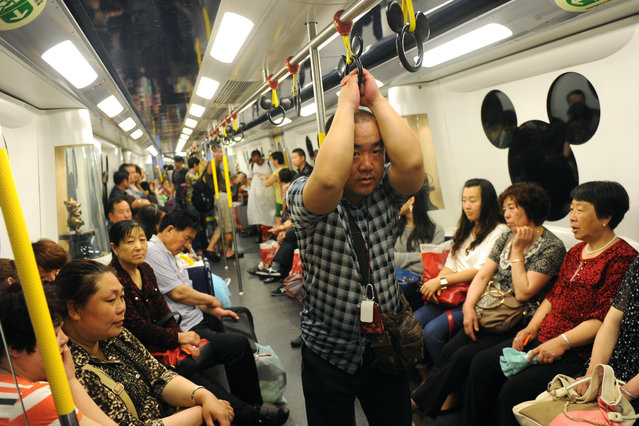 Mainland Chinese tourists ride on a uniquely designed subway train servicing Hong Kong's Disneyland on April 18, 2013. Hong Kong's once struggling Disneyland in February said it made a profit in 2012 for the first time since opening eight years ago, thanks to a surge in revenue as it welcomed a record number of visitors. (Photo by Aaron Tam/AFP Photo)