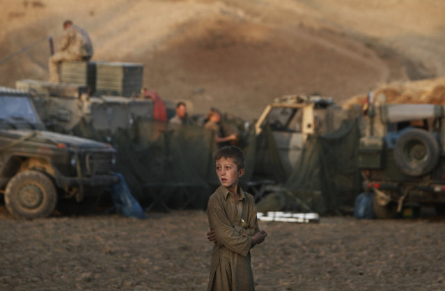 In this Monday, September 14, 2009 ile photo made by Associated Press photographer Anja Niedringhaus,an Afghan boy looks on as German ISAF soldiers prepare a temporary camp to overnight during a long term patrol in the mountainous region of Feyzabad, east of Kunduz, Afghanistan. (Photo by Anja Niedringhaus/AP Photo)
