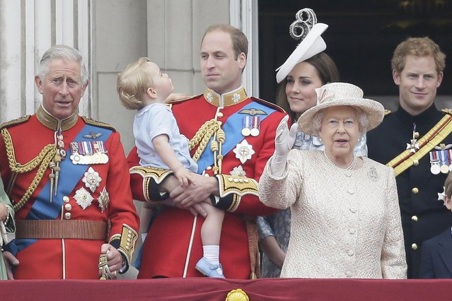 """Britain's Prince William holds his son Prince George, with Queen Elizabeth II, 2nd right, Kate, Duchess of Cambridge, the Prince of Wales, left, and Prince Harry, right, during the Trooping The Colour parade at Buckingham Palace, in London, Saturday, June 13, 2015. Hundreds of soldiers in ceremonial dress have marched in London in the annual Trooping the Color parade to mark the official birthday of Queen Elizabeth II. The Trooping the Color tradition originates from preparations for battle, when flags were carried or """"trooped"""" down the rank for soldiers to see. (AP Photo/Tim Ireland)"""