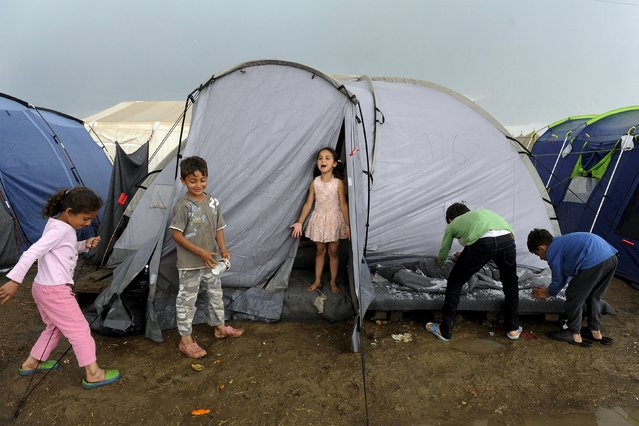 Children play outside a tent following heavy rainfall at a makeshift camp for migrants and refugees at the Greek-Macedonian border near the village of Idomeni, Greece, April 24, 2016. (Photo by Alexandros Avramidis/Reuters)