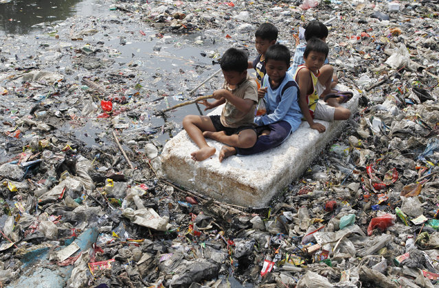 Children sitting on a makeshift raft play in a river full of rubbish in a slum area of Jakarta on September 19, 2012. (Photo by Enny Nuraheni/Reuters)