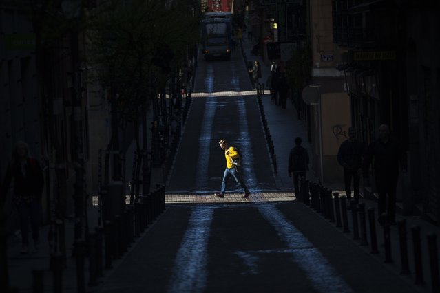 People walk along streets in Madrid, Tuesday, April 26, 2016. Spain's king is wrapping up two days of talks with political party leaders in a last-ditch bid to snap a four-month deadlock in finding a candidate capable of forming a government, but another election looks more likely. (Photo by Francisco Seco/AP Photo)