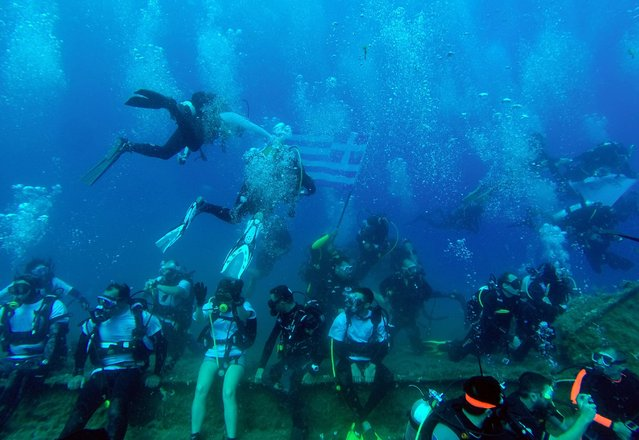 "A diver holds a Greek flag as other sit on the MS Zenobia shipwreck, a Swedish built ferry that capsized and sank off the coast of the Cypriot port city of Larnaca in 1979, as they participate in a ""Mass Dive"" event, consisting of over 120 divers, on June 28, 2015. (Photo by Emily Irving-Swift/AFP Photo)"