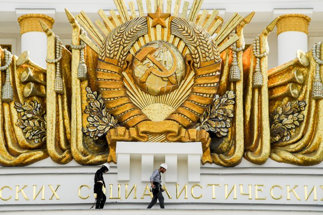 Workers fix a cornice close to Soviet Union state emblem atop the Central Pavilion at the All-Russia Exhibition Centre (VDNKh), a trade show and amusement park in Moscow on August 8, 2019. VDNKh, the Soviet-era outdoor exhibition centre, marks its 80th anniversary this summer. (Photo by Kirill Kudryavtsev/AFP Photo)