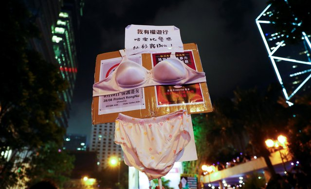 """Protesters carry a placard as they gather to condemn alleged sexual harassment of a detained demonstrator at a police station, in Hong Kong, China on August 28, 2019. Placard reads: """"I don't want police taking all my clothes including my bra"""". (Photo by Kai Pfaffenbach/Reuters)"""