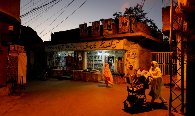 Resident walk past a shop during sunset hours along a street in Mariabad, Quetta, Pakistan, June 17, 2019. (Photo by Akhtar Soomro/Reuters)