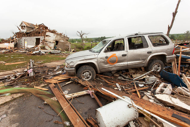 Piles of cars and remnants of homes sit along Highway 64 in Vilonia, Ark., Monday, April 28, 2014, after a tornado struck the town late Monday. Vilonia was hit hard Sunday after a tornado system ripped through several states in the central U.S. and left more than a dozen dead in a violent start to this year's storm season, officials said. (Photo by Karen E. Segrave/AP Photo)