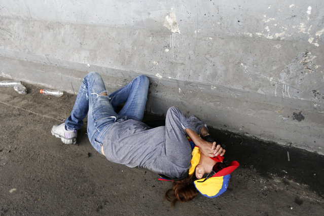 A demonstrator lies on the ground overcome by tear gas during anti-government protests in Caracas, Venezuela, Wednesday, April 19, 2017. (Photo by Ariana Cubillos/AP Photo)
