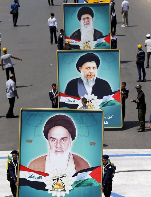 Iraqi Shiite Muslim men from Hashid Shaabi (Popular Mobilization) hold portraits of (front to back) Iran's late leader Ayatollah Ruhollah Khomeini, Iraq's late Shi'ite cleric Mohammed Baqir al-Sadr, and Supreme Leader Ayatollah Ali Khamenei during a parade marking the annual al-Quds Day, or Jerusalem Day, on the last Friday of the Muslim holy month of Ramadan in Baghdad, July 10, 2015. (Photo by Thaier al-Sudani/Reuters)