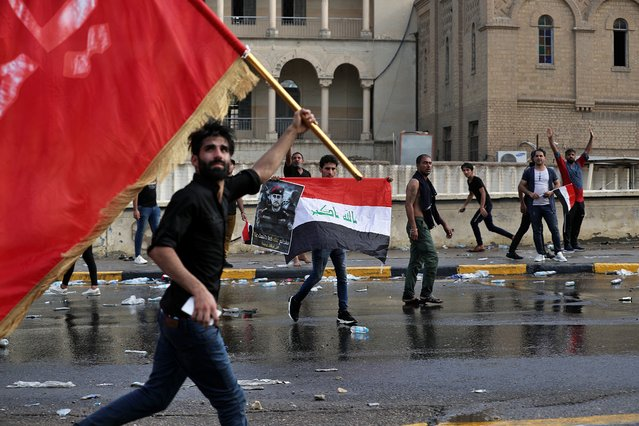Protestors wave flags and hold a poster of Lt. Gen. Abdul-Wahab al-Saadi during a protest in Tahrir Square, in central Baghdad, Iraq, Tuesday, October 1, 2019. (Photo by Khalid Mohammed/AP Photo)