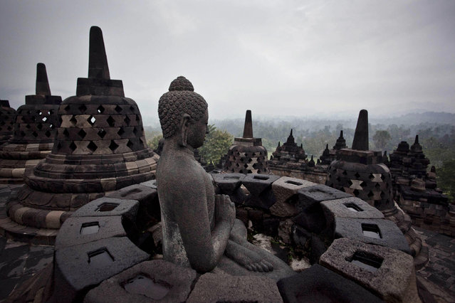 "A Buddha statue is seen at Borobudur temple during celebrate Vesak Day, commonly known as ""Buddha's birthday"", at the Borobudur Mahayana Buddhist monument on May 6, 2012 in Magelang, Indonesia. (Photo by Ulet Ifansasti/Getty Images)"