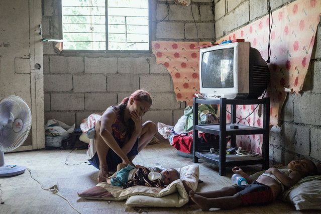 Jojo tends to her children in her home in Angeles City. (Photo by Hannah Reyes Morales/The Washington Post)