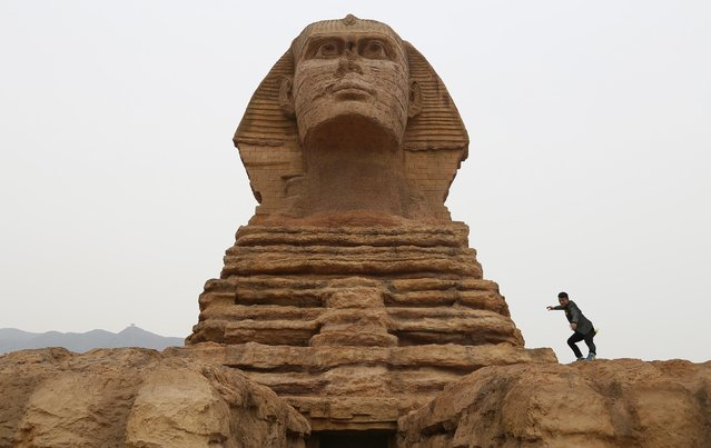 A man poses for photographs on a full-scale replica of the Sphinx, that is part of an unfinished theme park that will also accommodate the production of movies, television shows and animation, on the outskirts of Shijiazhuang, Hebei province May 10, 2014. The replica is a venue of a film studio which is already functioning. The theme park is scheduled to open this October, local media reported. (Photo by Reuters/Stringer)