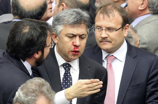 Member of parliament from the main opposition Republican People's Party (CHP) Ali Ihsan Kokturk's nose bleeds as MPs from the ruling AK Party (AKP) and CHP scuffle during a debate on a draft law which will give the government tighter control over the appointment of judges and prosecutors, at a parliamentary session in Ankara, Turkey, February 15, 2014. (Photo by Reuters/Stringer)