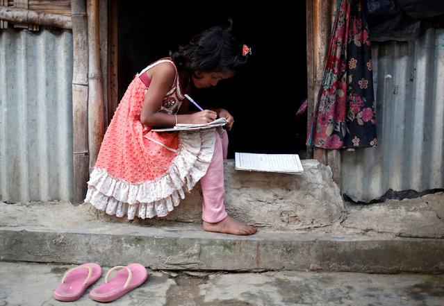 A Rohingya refugee girl studies on her doorstep at Leda Unregistered Refugee Camp in Teknaf, Bangladesh, February 15, 2017. (Photo by Mohammad Ponir Hossain/Reuters)