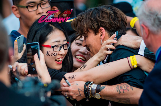 "Actor Johnny Depp hugs two fans as he arrives for the world premiere of Disney movie ""Pirates of the Caribbean: Dead Men Tell No Tales"" in Shanghai on May 11, 2017. (Photo by Johannes Eisele/AFP Photo)"