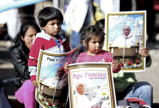 Children hold posters of Pope Francis before he arrives to visit the El Quinche Santuary near Quito, Ecuador, July 8, 2015. (Photo by Alessandro Bianchi/Reuters)