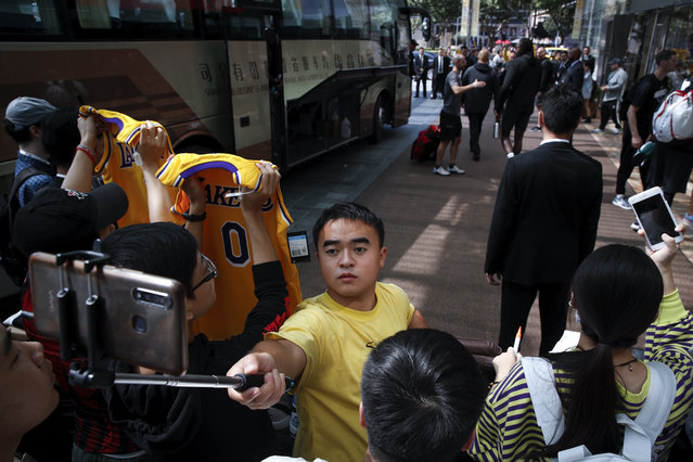 Fans take smartphone selfies and show off their LA Lakers jerseys as NBA players step out from a bus outside the Ritz-Carlton hotel in Shanghai, China, Thursday, October 10, 2019. NBA Commissioner Adam Silver told the Brooklyn Nets and Los Angeles Lakers on Wednesday that the league is still expecting them to play as scheduled this week, even while the rift between the league and Chinese officials continued in ways that clearly suggested the two planned games in Shanghai and Shenzhen were anything but guaranteed. (Photo by Andy Wong/AP Photo)