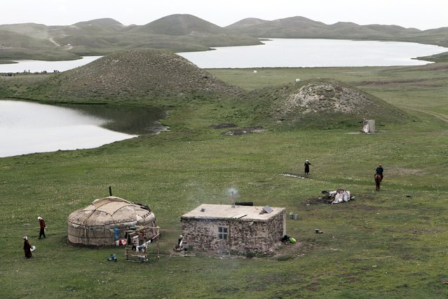 People stand at a traditional settlement set up during the Kyrgyz national horse games and festival near the Tulpar-Kul lake in the Chon Alai mountain range, some 3500 metres (11483 feet) above sea level, in the Osh region of Kyrgyzstan, July 25, 2015. (Photo by Vladimir Pirogov/Reuters)
