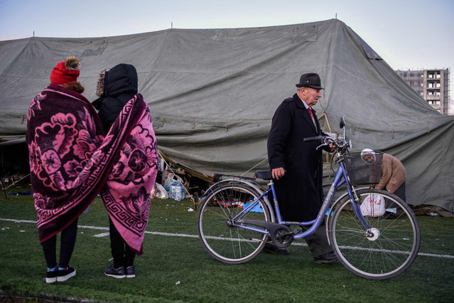 People stroll at a makeshift camp at the soccer stadium in Durres, western Albania, on November 27, 2019, after the strongest earthquake in decades claimed at least 20 lives, with victims trapped in the debris of toppled buildings. Albania was in national mourning on November 27 as emergency workers continued to pull bodies from the ruins of buildings gutted by a violent earthquake, with nearly 30 dead found so far and more than 40 rescued alive. Tirana declared a state of emergency in the areas hardest-hit by the November 26 pre-dawn earthquake: the coastal city of Durres and the town of Thumane, where victims were trapped by toppled buildings. (Photo by Armend Nimani/AFP Photo)