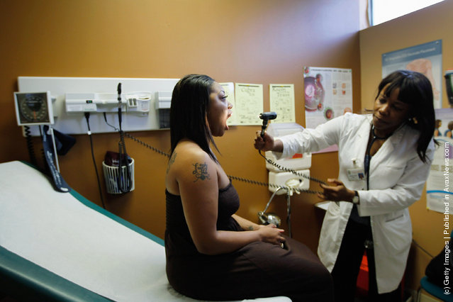 Marche Curry (L), who is a college student and unable to afford insurance, is examined by Dr. Nadine Altidor during a routine checkup at the Jessie Trice Center for Community Health clinic