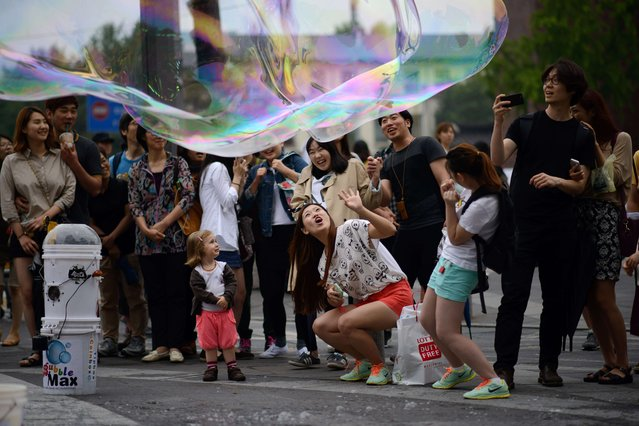 Tourists react to a large bubble created by a street performer in Seoul on June 2, 2014. The number of foreign travellers to South Korea has steadily grown over the years and topped 10 million for the first time in 2012. (Photo by Ed Jones/AFP Photo)