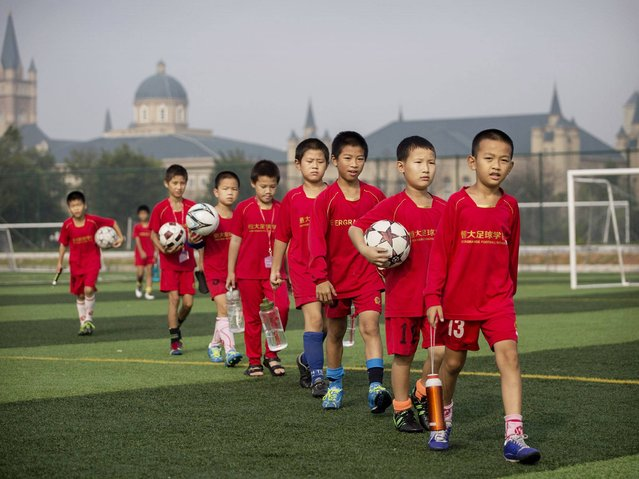 Young Chinese football players walk to training at the Evergrande International Football School near Qingyuan in Guangdong Province. (Photo by Kevin Frayer/Getty Images)