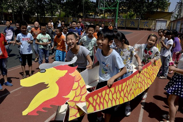 """This photo taken on May 25, 2017 shows students competing as they carry dragon boats made of paper during a race to celebrate the upcoming Dragon Boat Festival, at a primary school in Liaocheng, in eastern China' s Shandong province The dragon boat festival, also called """"duanwu"""", takes place on the fifth day of the fifth month of the Chinese lunar calendar. (Photo by AFP Photo/Stringer)"""