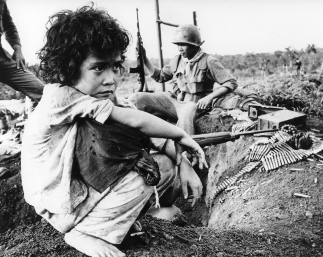 A Vietnamese girl, her parents slain in a ferocious Viet Cong attack on Dong Xoai, sits with her personal belongings on a mud wall of the village, staring into the jungle after the fight subsided, June 10, 1965. A Vietnamese soldier stands guard in the background. (Photo by Horst Faas/AP Photo)