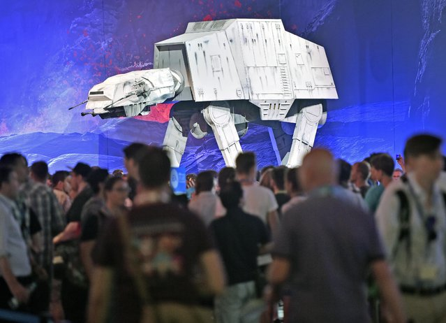 Visitors walk near  a Star Wars AT-AT at the gamescom  computer game fair in Cologne, Germany, Wednesday, August 5, 2015. (Photo by Martin Meissner/AP Photo)