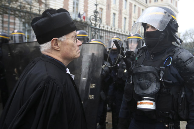 A lawyer faces a riot police officer during a demonstration in Rennes, western France, Thursday January 9, 2020. French rail workers, teachers, doctors, lawyers and others joined the fourth nationwide day of protests and strikes on Thursday to denounce President Emmanuel Macron's plans to overhaul the pension system. (Photo by David Vincent/AP Photo)