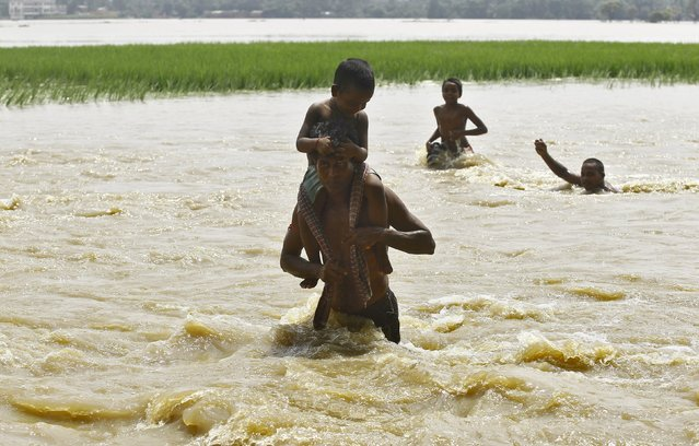 People wade through the flood waters at Howrah district in West Bengal, India, August 5, 2015. At least 75 people have died and tens of thousands have had to take refuge in state-run relief camps after heavy rains caused floods and landslides in eastern India, government officials and aid groups said on Monday. (Photo by Rupak De Chowdhuri/Reuters)
