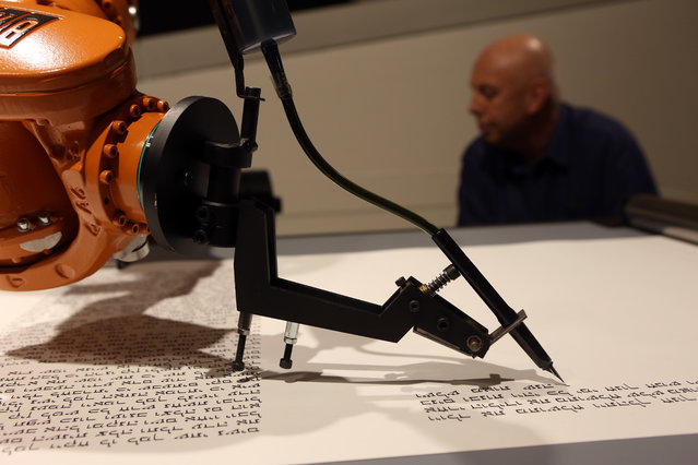 "An industrial robot, an installation work called ""bios (torah)"" by the artist group robotlab, begins writing a Torah on July 10, 2014 in the Jewish Museum in Berlin, Germany. At the speed of a human, the robot writes a total of 304,805 Hebrew letters on an 80-meter roll of paper. The finished scroll, to be complete in January 2015, will not be considered halakhic, or meeting the requirements for use for religious purposes. (Photo by Adam Berry/Getty Images)"
