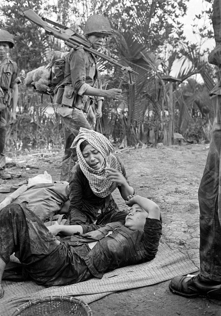 As South vietnamese troops pass by in the Ca Mau peninsula, a mother grieves over her daughter, who was badly wounded by machine gun fire from a U.S. helicopter, the week of Sept. 15, 1963