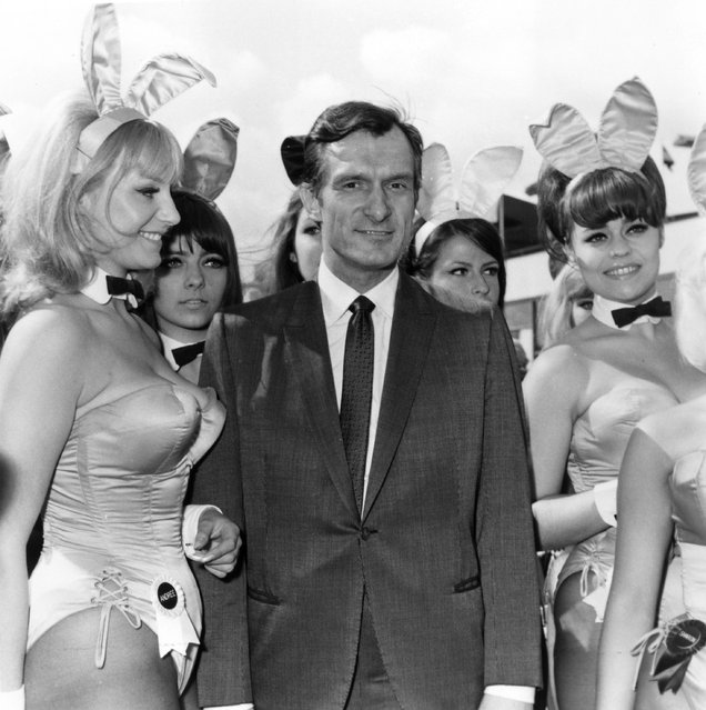 Playboy editor and tycoon Hugh Hefner is greeted by a group of bunny girls from his Playboy Clubs, upon his arrival at London Airport, 1966. (Photo by Dove/Getty Images)