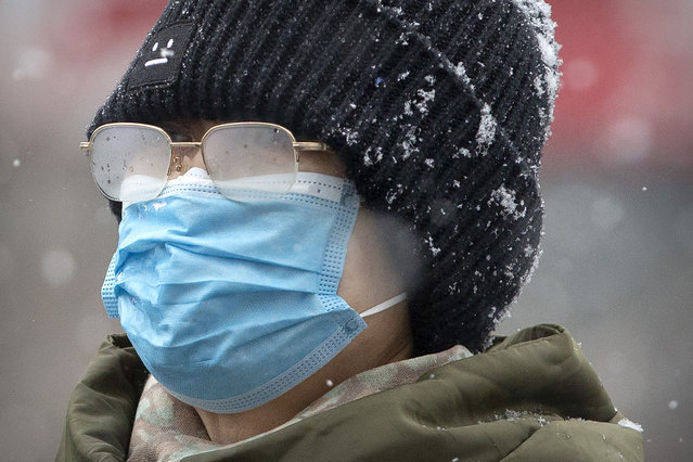 A woman's eyeglasses are fogged up as she wears a face mask during a snowfall in Beijing, Sunday, February 2, 2020. China's death toll from a new virus increased to 304 on Sunday amid warnings from the World Health Organization that other countries need to prepare in the event the disease spreads among their populations as more nations report local infections. (Photo by Mark Schiefelbein/AP Photo)
