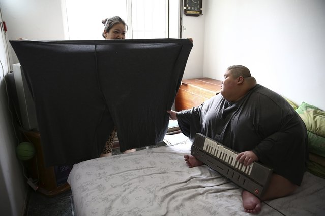 Zhang Hangjun, 20, looks as his mother displays his pants in Shenyang, Liaoning province, China, on Jule 25, 2014. Zhang, who currently weighs about 551 pounds, and his twin brother were diagnosed with cerebral palsy after they were born. Zhang has had to spend most of his life on a bed as the family is unable to afford medical treatment for him, local media reported. (Photo by Sheng Li/for Reuters)