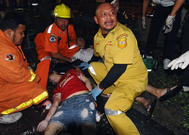 Thai emergency staff help the injured after the scene of an explosion near Erawan Shrine, central Bangkok, Thailand, 17 August 2015. An explosion in a busy commercial district in the Thai capital killed at least 15 people. Witnesses said the explosion happened around 7:15 pm (12:15 GMT) at the Rajprasong Intersection, a business area famous among tourists and locals for a revered Hindu shrine. (Photo by EPA/Stringer)
