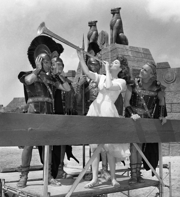 "An up to date Sappho, Hollywood film star Tina Louise, makes like a trumpet blower on the set of ""Sappho, Venus of Lesbos"" in Rome, Italy, July 15, 1960. Actors in the parts of ancient soldiers play up to the off-camera bit. Tina plays the role of Sappho, the beautiful Greek poetess. (Photo by AP Photo)"