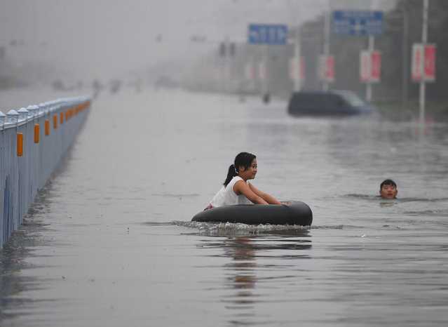 A girl sitting on a tyre plays at a flooded street, as a man swims near her in Xinxiang, Henan Province, China, July 9, 2016. (Photo by Reuters/Stringer)