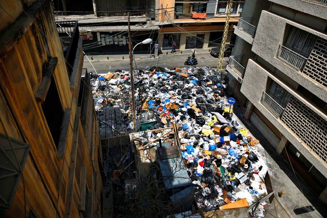 A motorcycle passes by a large pile of garbage blocking a street in Beirut, Lebanon, Monday, July 27, 2015. Protesters have closed the highway linking Beirut with southern Lebanon over the country's trash crisis. (Photo by Hassan Ammar/AP Photo)